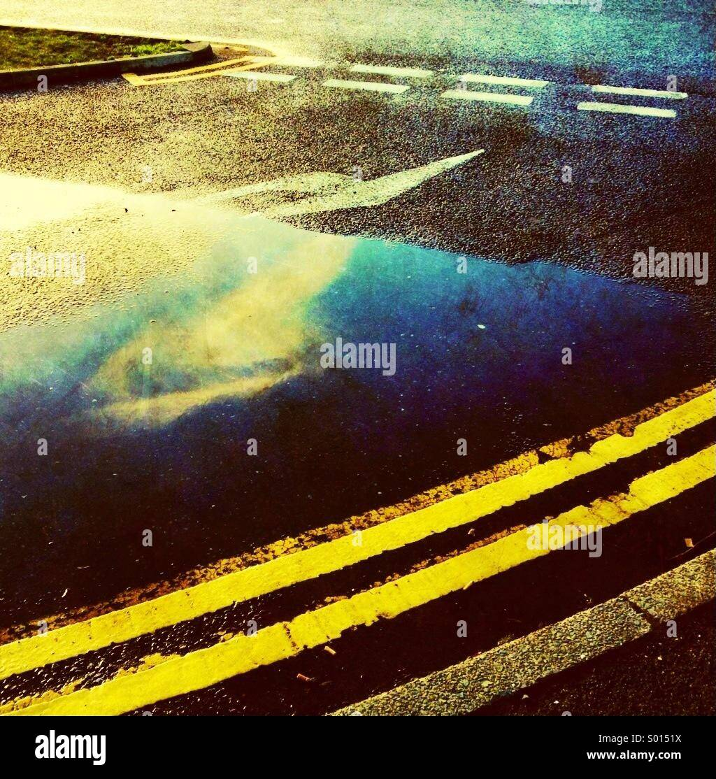 Double yellow lines and reflection of cloud in puddle - Stock Image