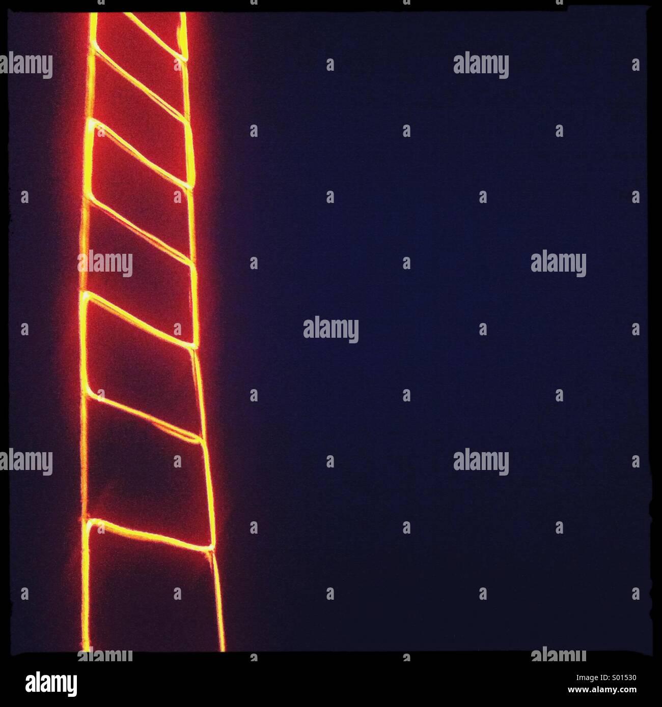 Orange led let up ladder on black background - Stock Image