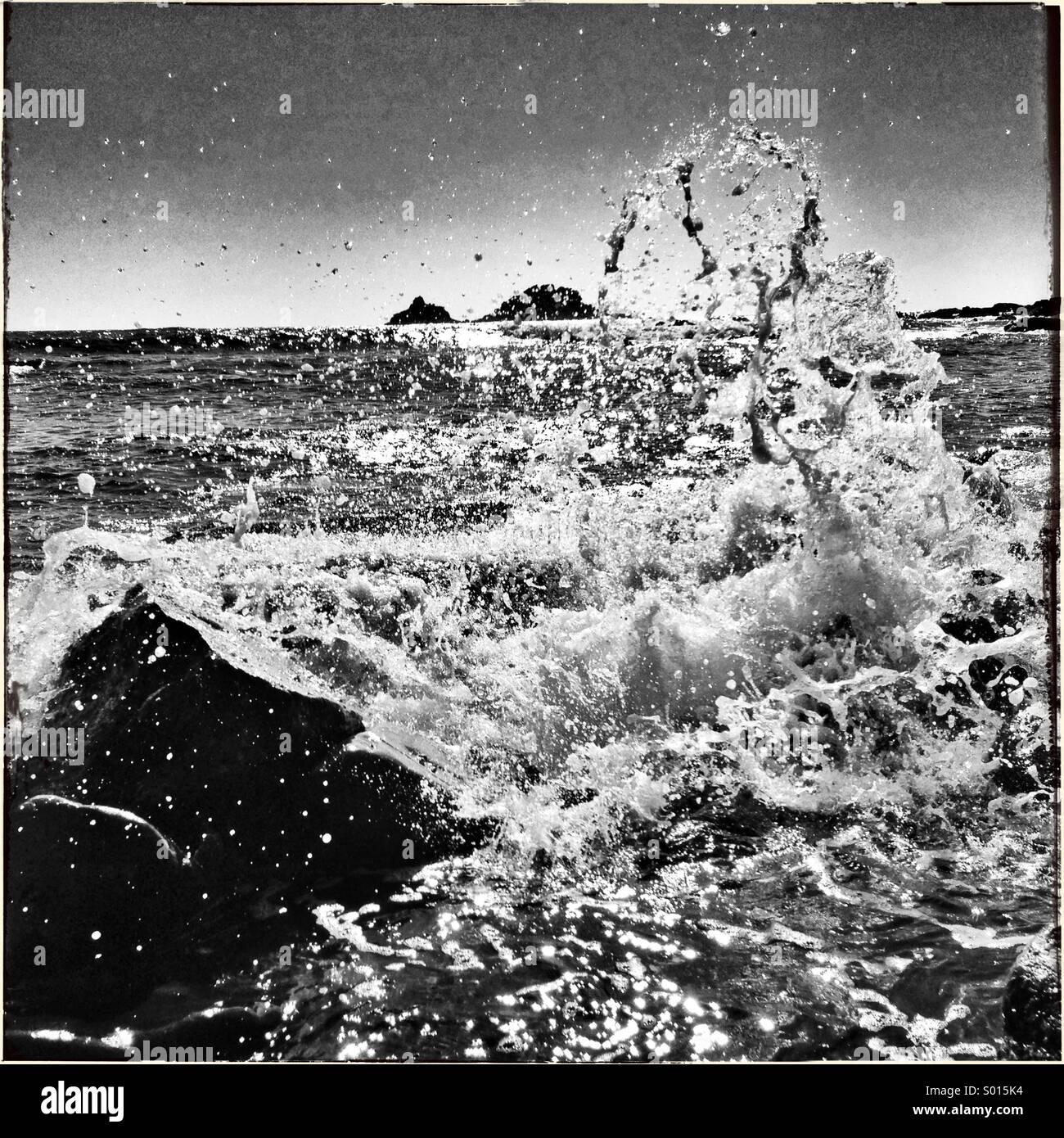 Black and white image of water splashing on rocks - Stock Image