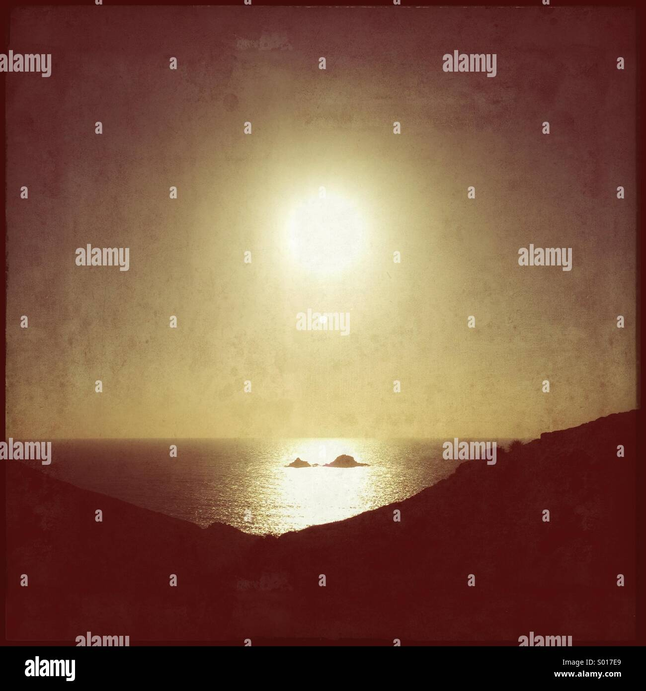 Sun down over rocky island - Stock Image