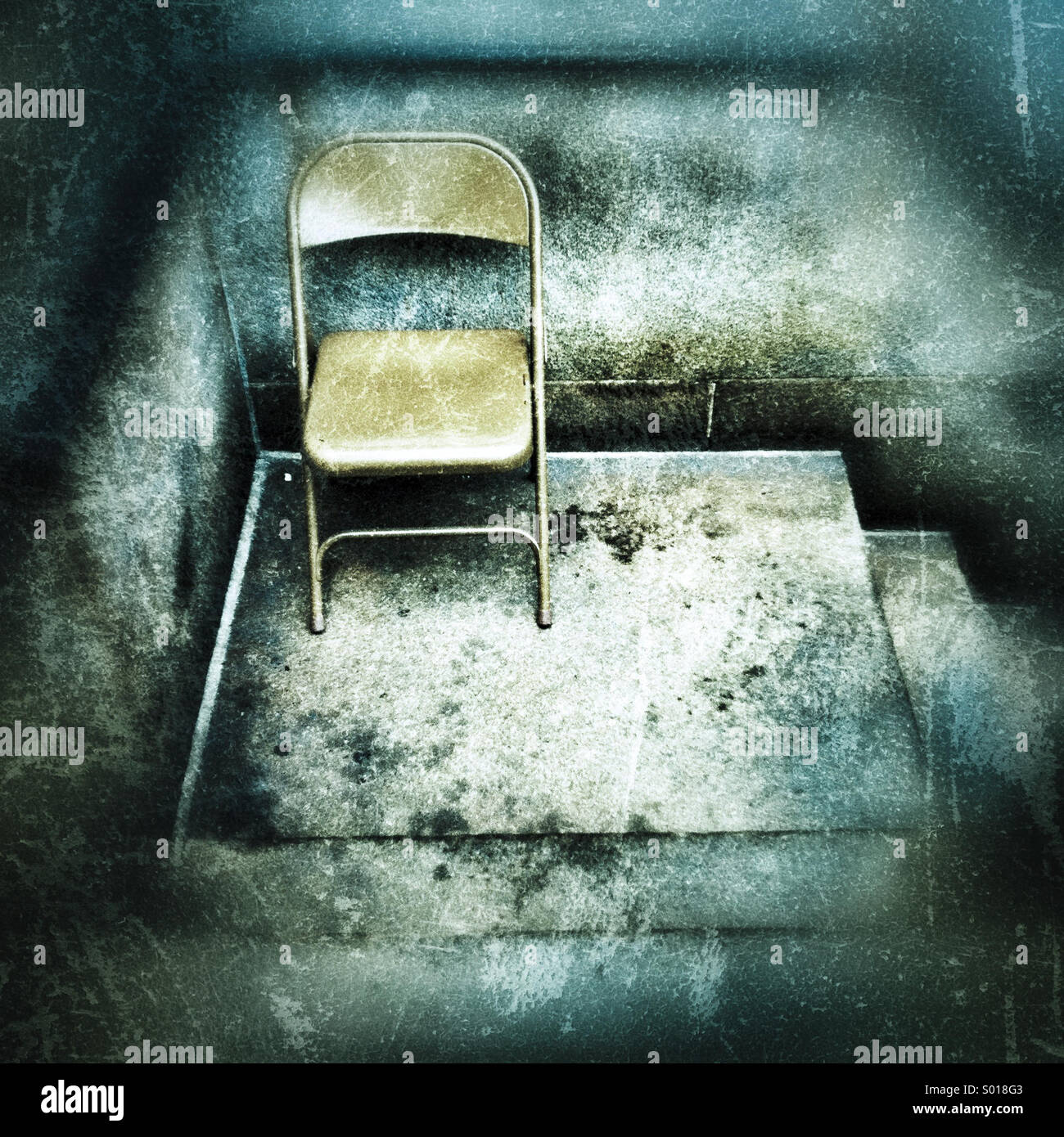 A metal folding chair sitting on a distressed looking cement stoop - Stock Image