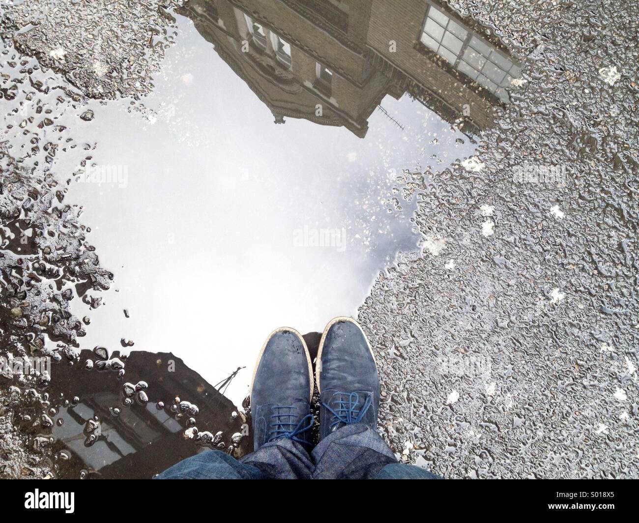 Standing at puddle in london - Stock Image