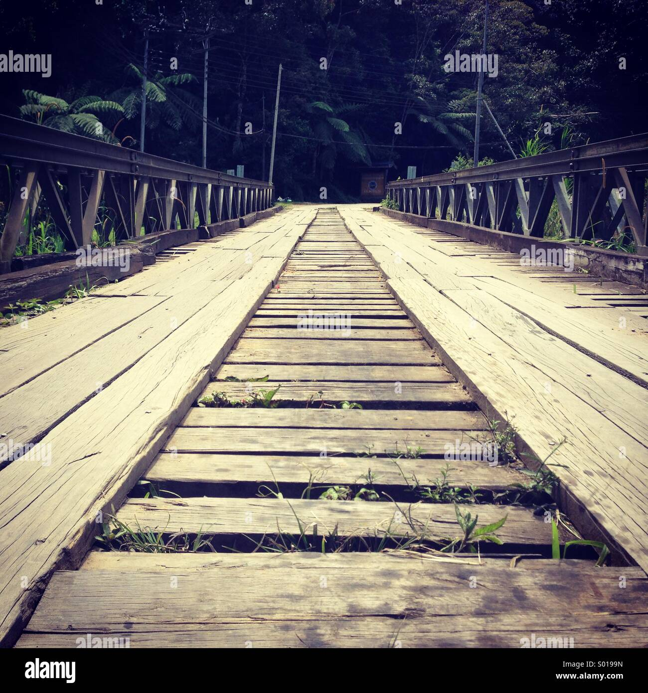 An old wooden bridge still used today for crossing a river to the otherside. - Stock Image