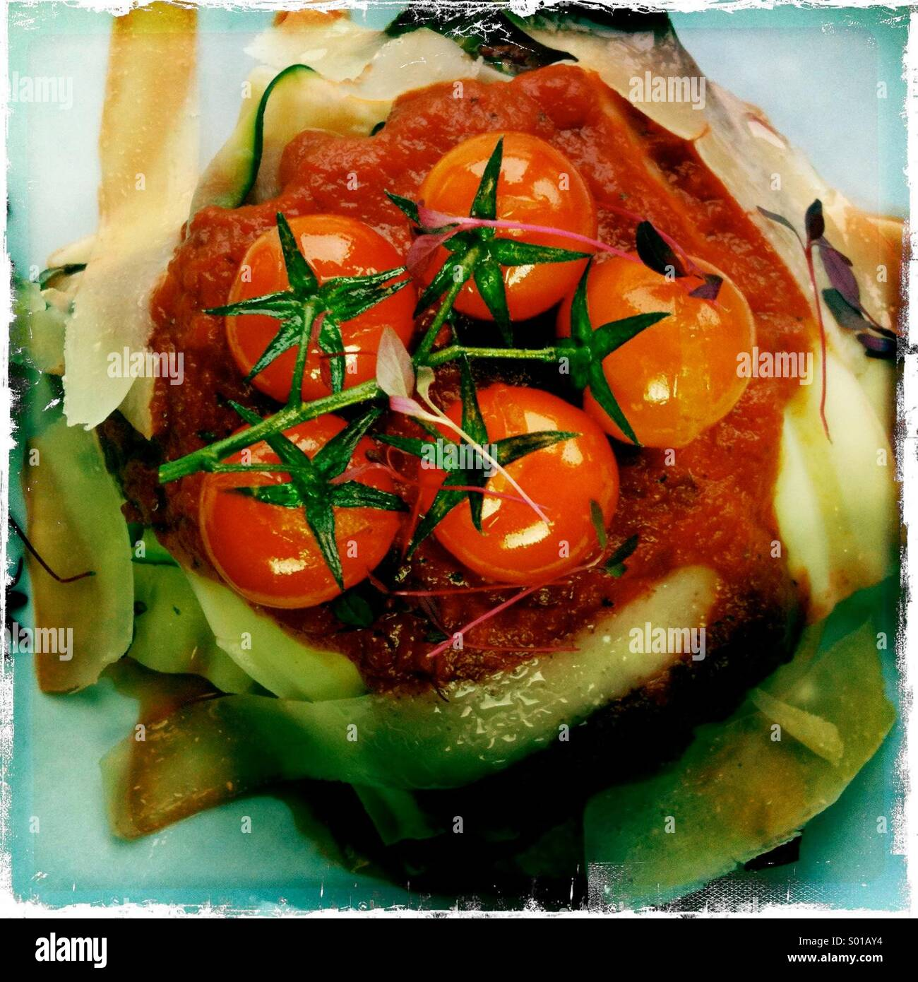 Open vegetable lassagne eith rich tomatoe and herb sauce served with garlic slice - Stock Image
