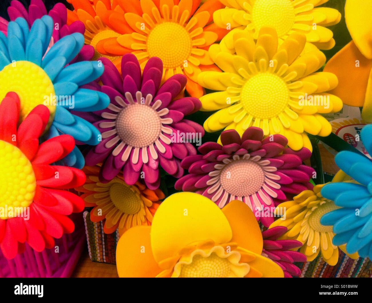 A colorful photograph of plastic daisies - Stock Image