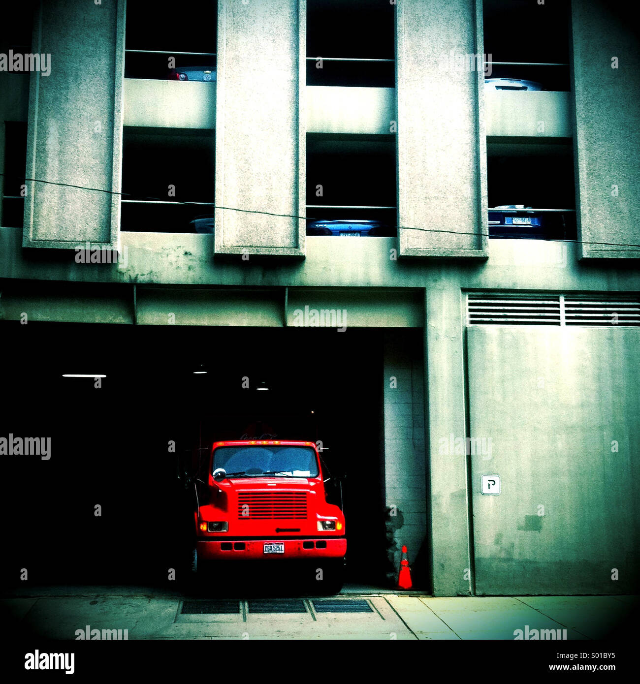 A red dump truck is parked in the entry to a parking garage - Stock Image