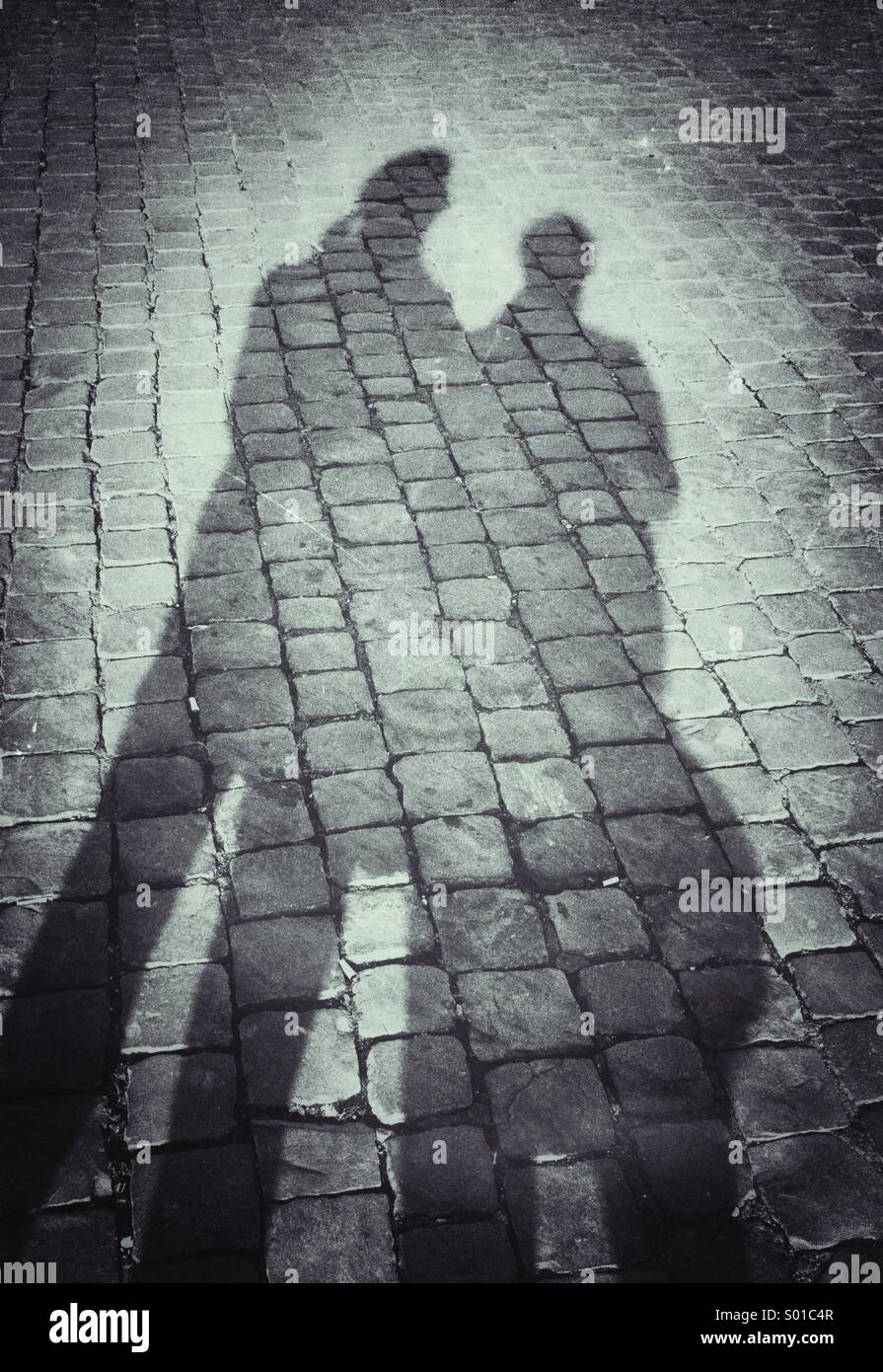 Shadow of a man and woman on cobbles - Stock Image