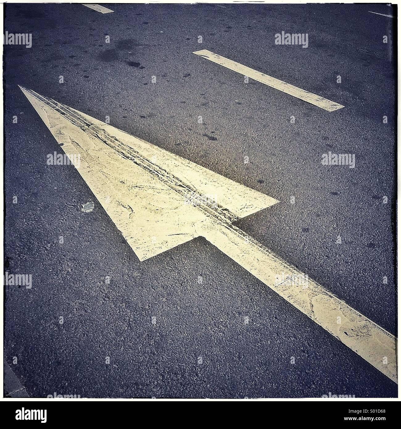 Arrow on asphalt road, one direction traffic signStock Photo