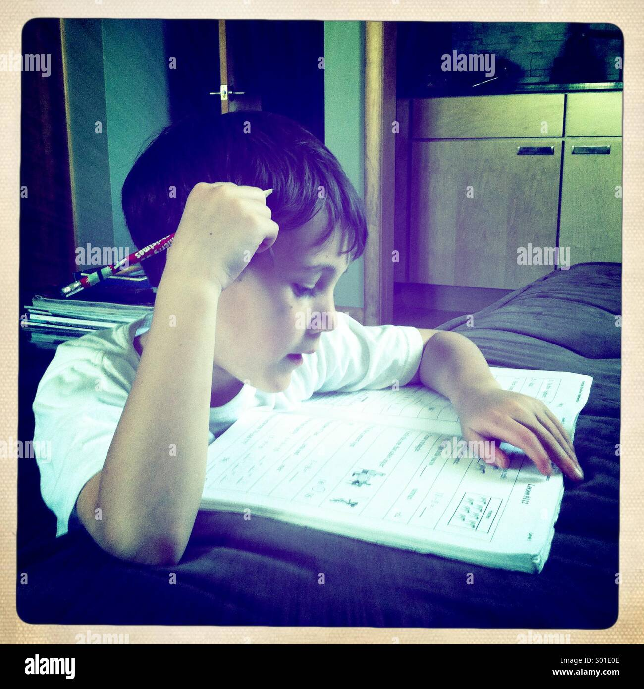 Boy doing his homework. - Stock Image