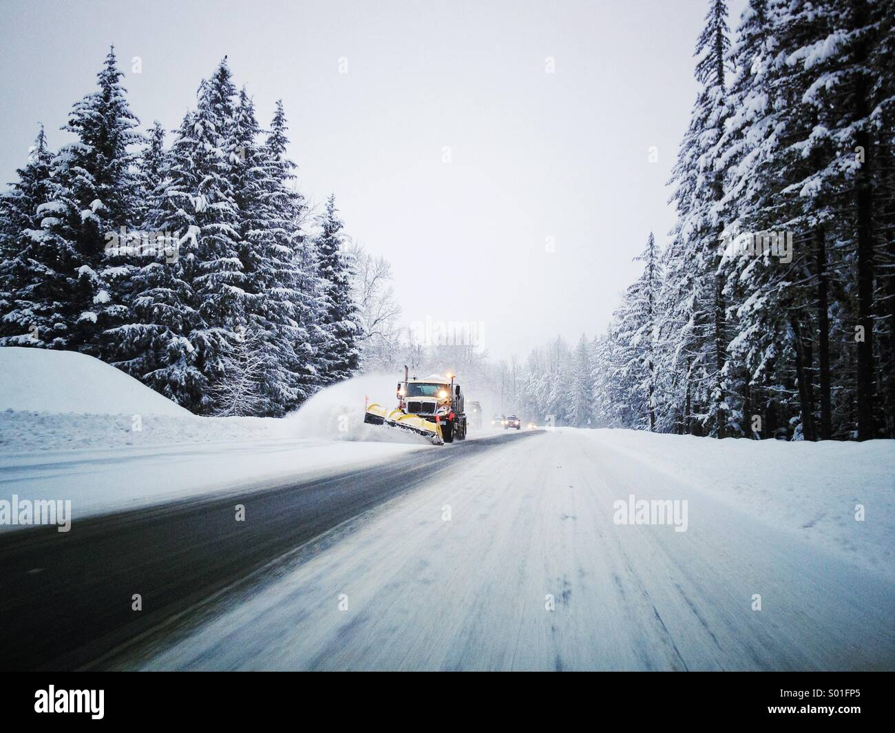 Snowplow clearing wintertime roadway. - Stock Image