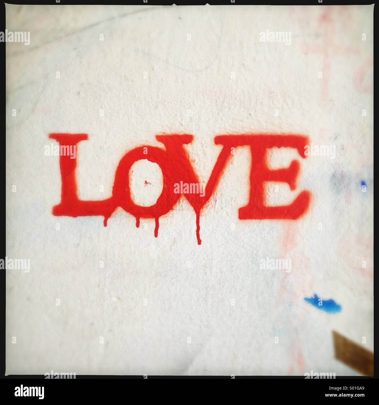 'Love' as red stencil graffiti on a white wall. - Stock Image