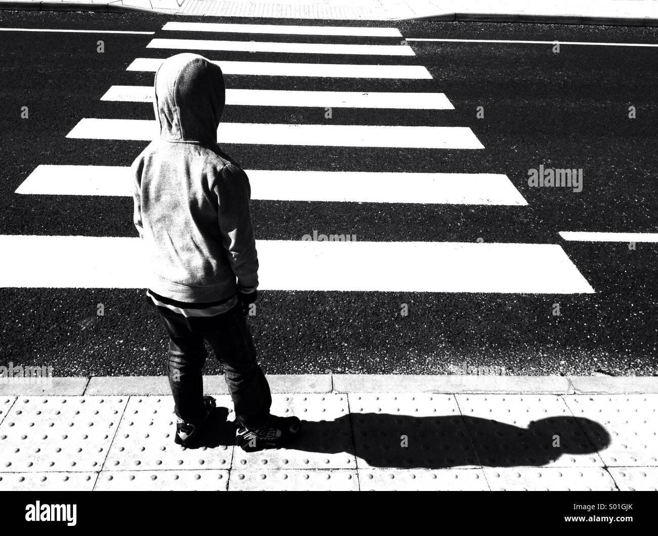 Boy waiting at zebra crossing Stock Photo