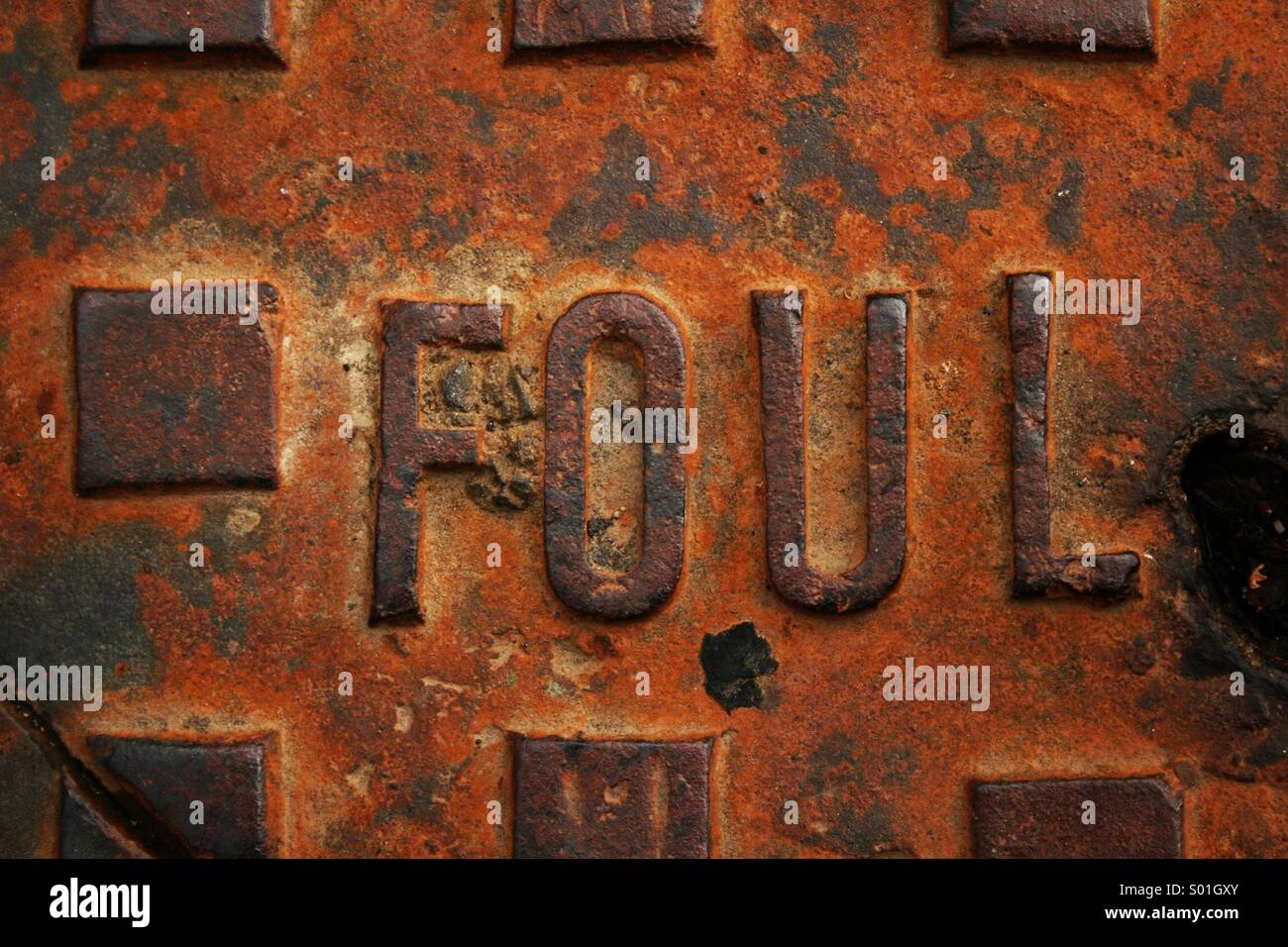 Rusty foul waste manhole cover - Stock Image