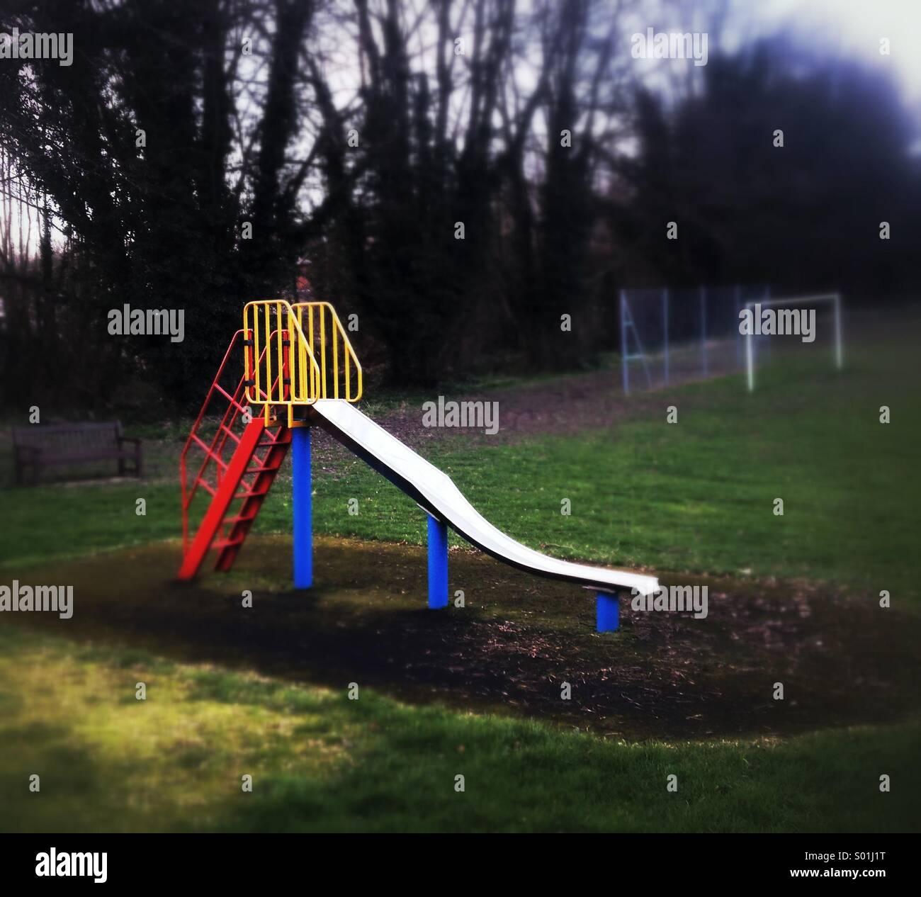 Children's slide in empty playground Stock Photo