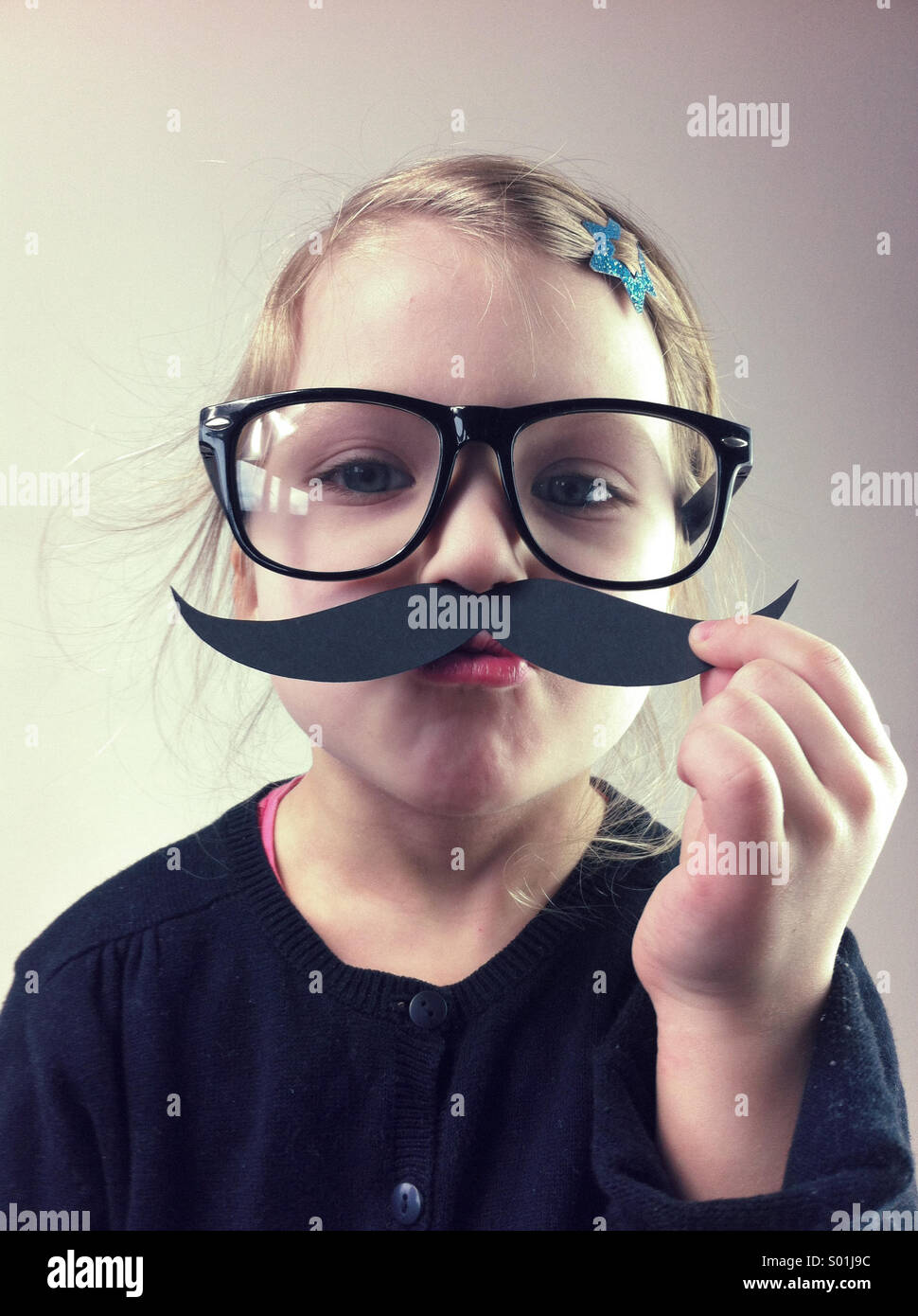 Little girl with big glasses and paper mustaches - Stock Image
