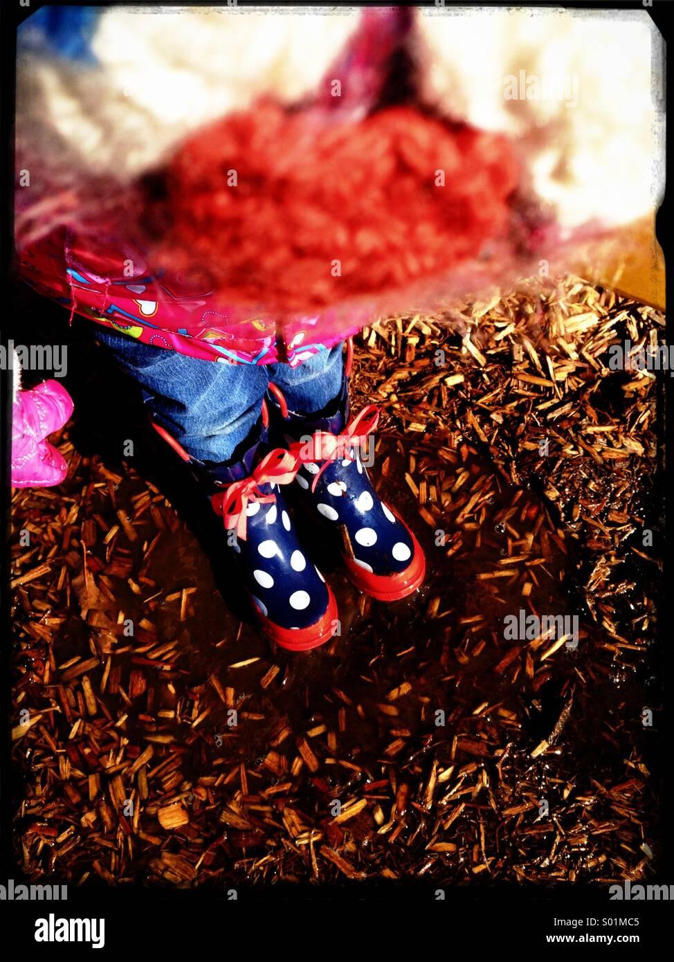 Little girl in polka dot rain boots. - Stock Image