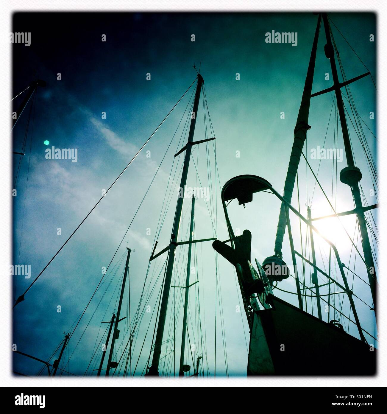 Boat masts silhouetted against a blue sky - Stock Image