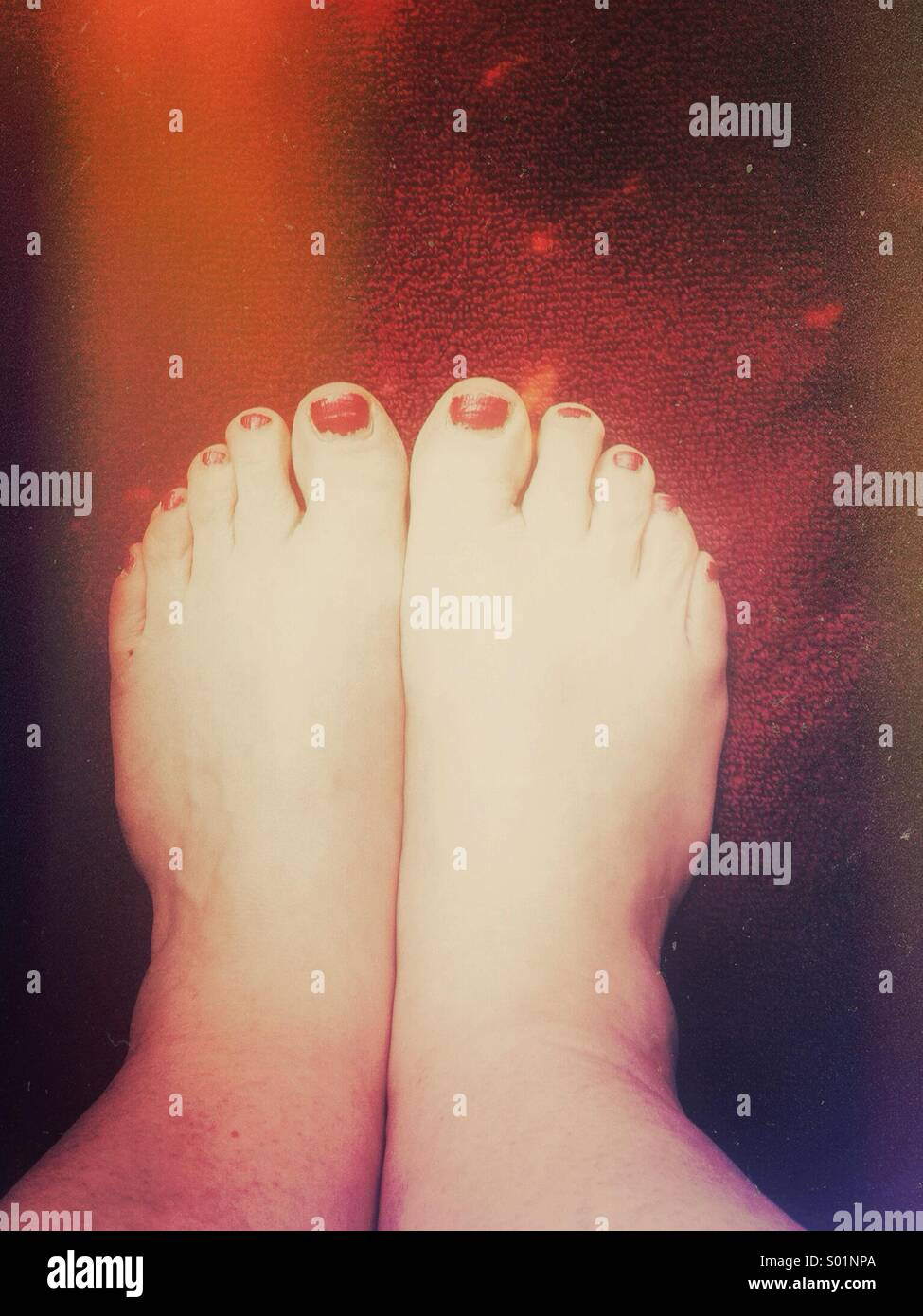 Chipped red nail polish and bare wide feet on red towel. - Stock Image