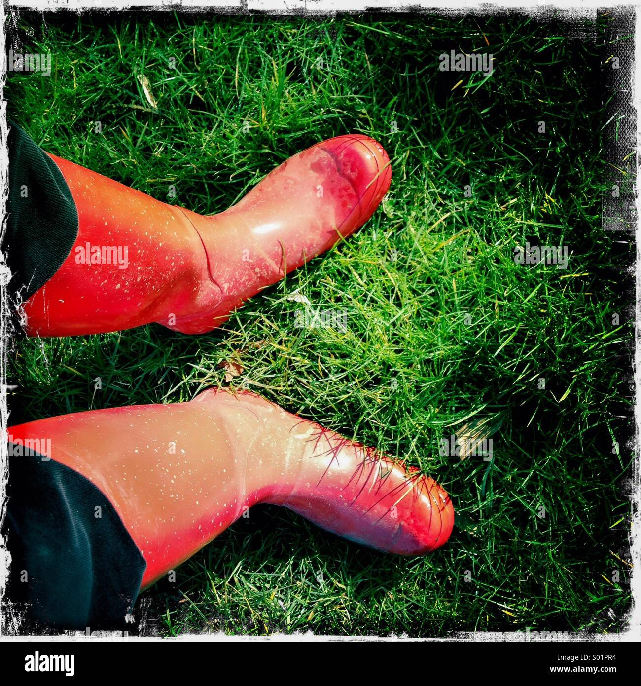 Muddy Red Wellington boots on wet, sodden grass. Hipstamatic  iPhone. - Stock Image