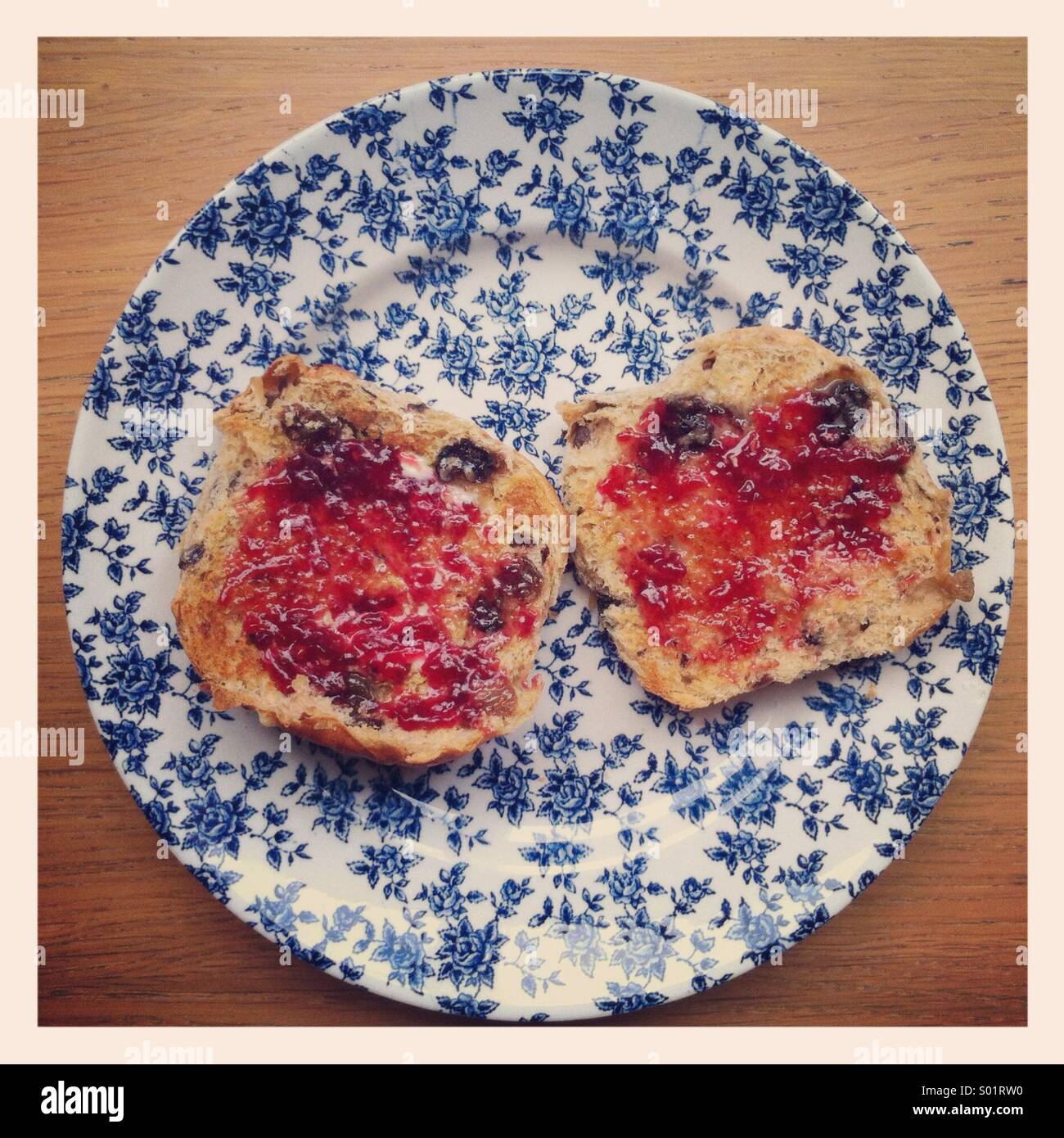 Jam on two toasted halves of a hot cross bun, on a vintage blue and white floral plate. - Stock Image