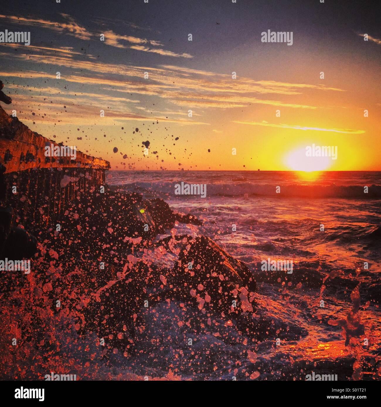 Huge wave crashing onto rocks during sunset. - Stock Image