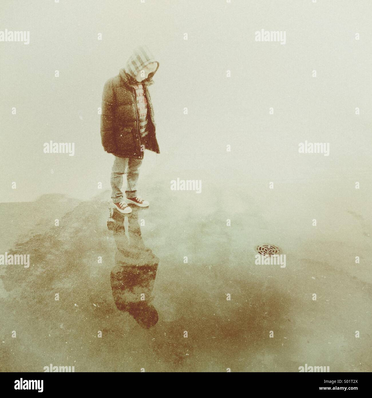 Young boy stood in a puddle looking at his reflection before the water goes down the nearby drain - Stock Image