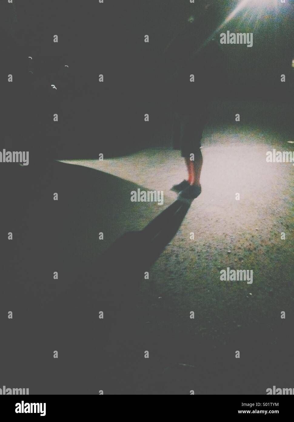 Man standing in shadows - Stock Image