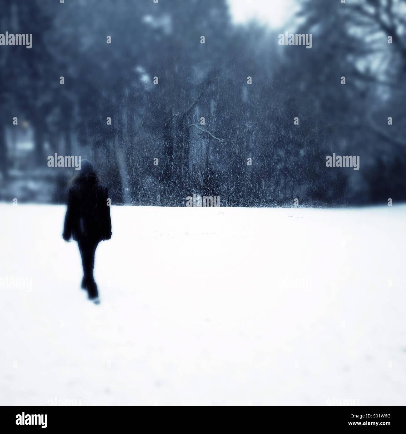 girl walking in snow - Stock Image