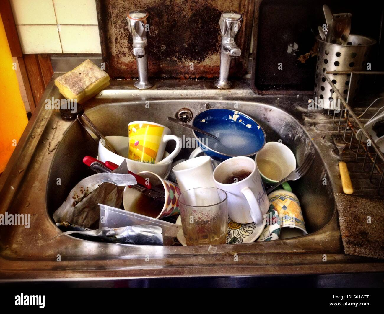 Washing up in a squalid student flat - Stock Image