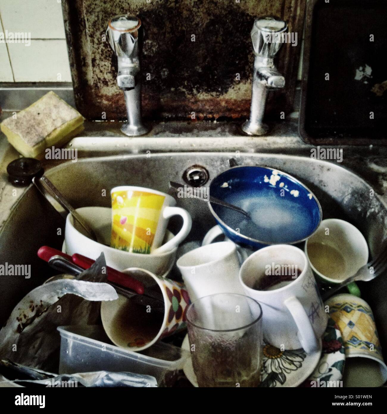 Close up of squalid kitchen sink full of dirty dishes - Stock Image