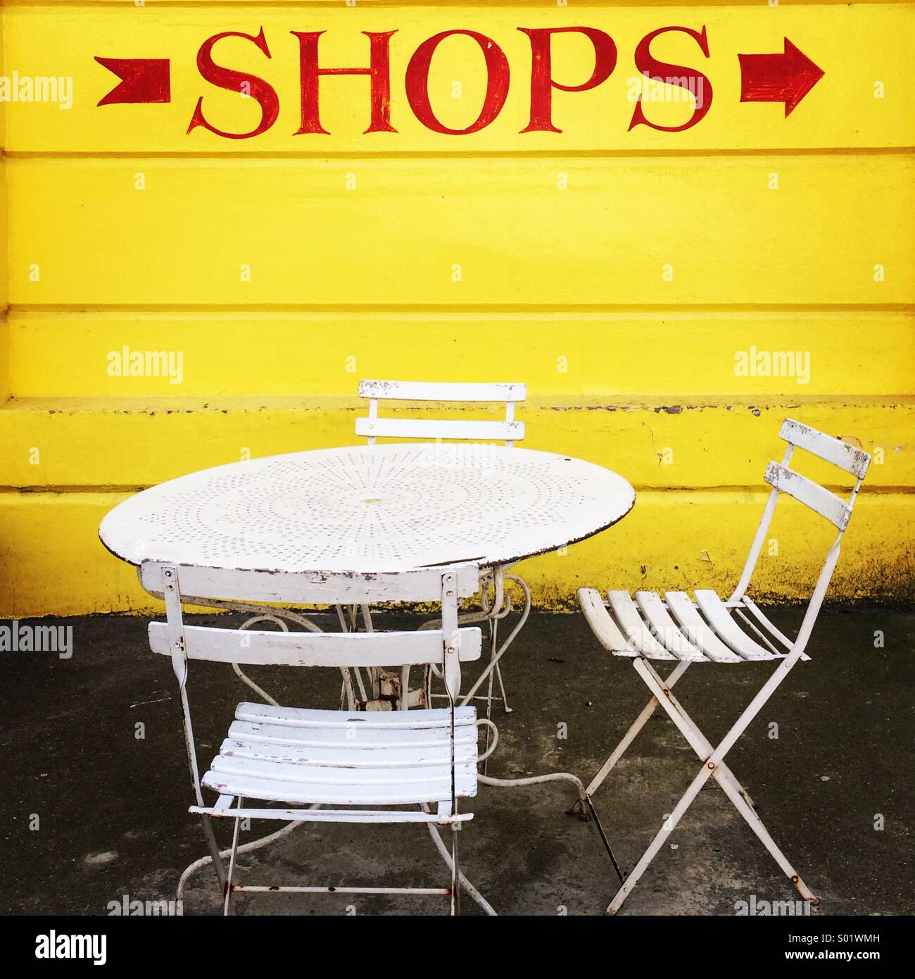 Sign for shops on yellow wall with white garden chairs and table - Stock Image