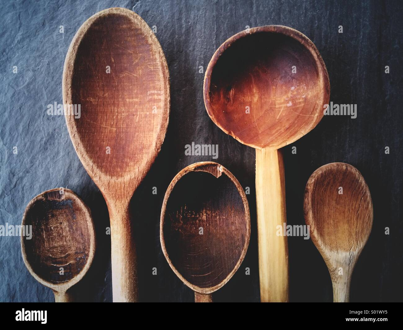 Beautiful old wooden spoons for cooking on a slate background. - Stock Image