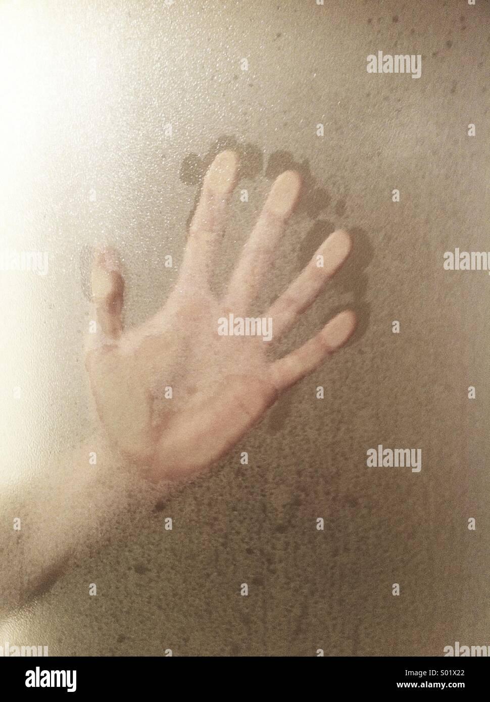 Hand against shower door - Stock Image