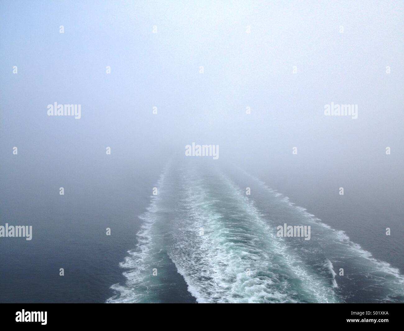 Ferry boat wake disappearing into the fog. - Stock Image