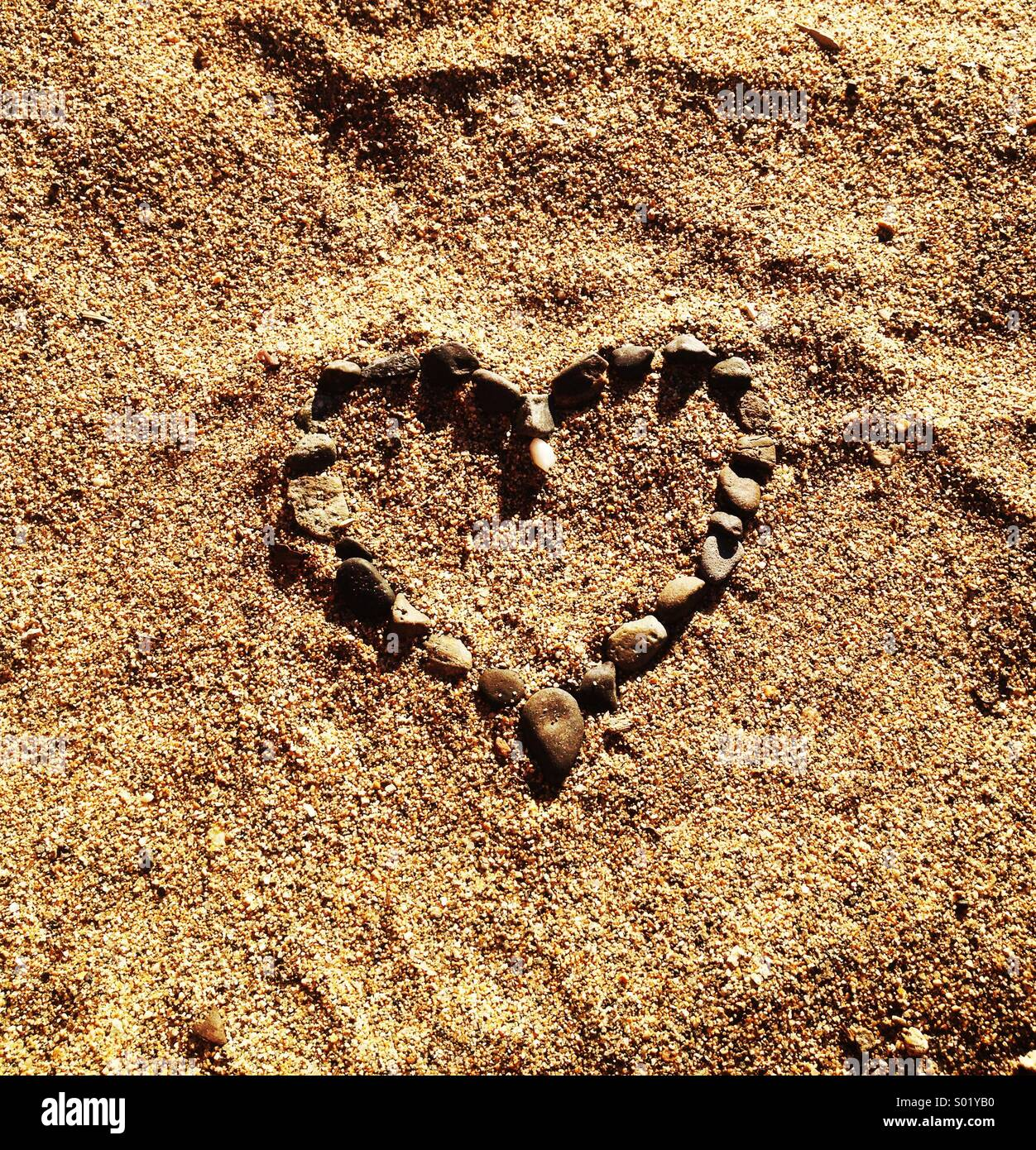 Heart made of pebbles in the sand. - Stock Image