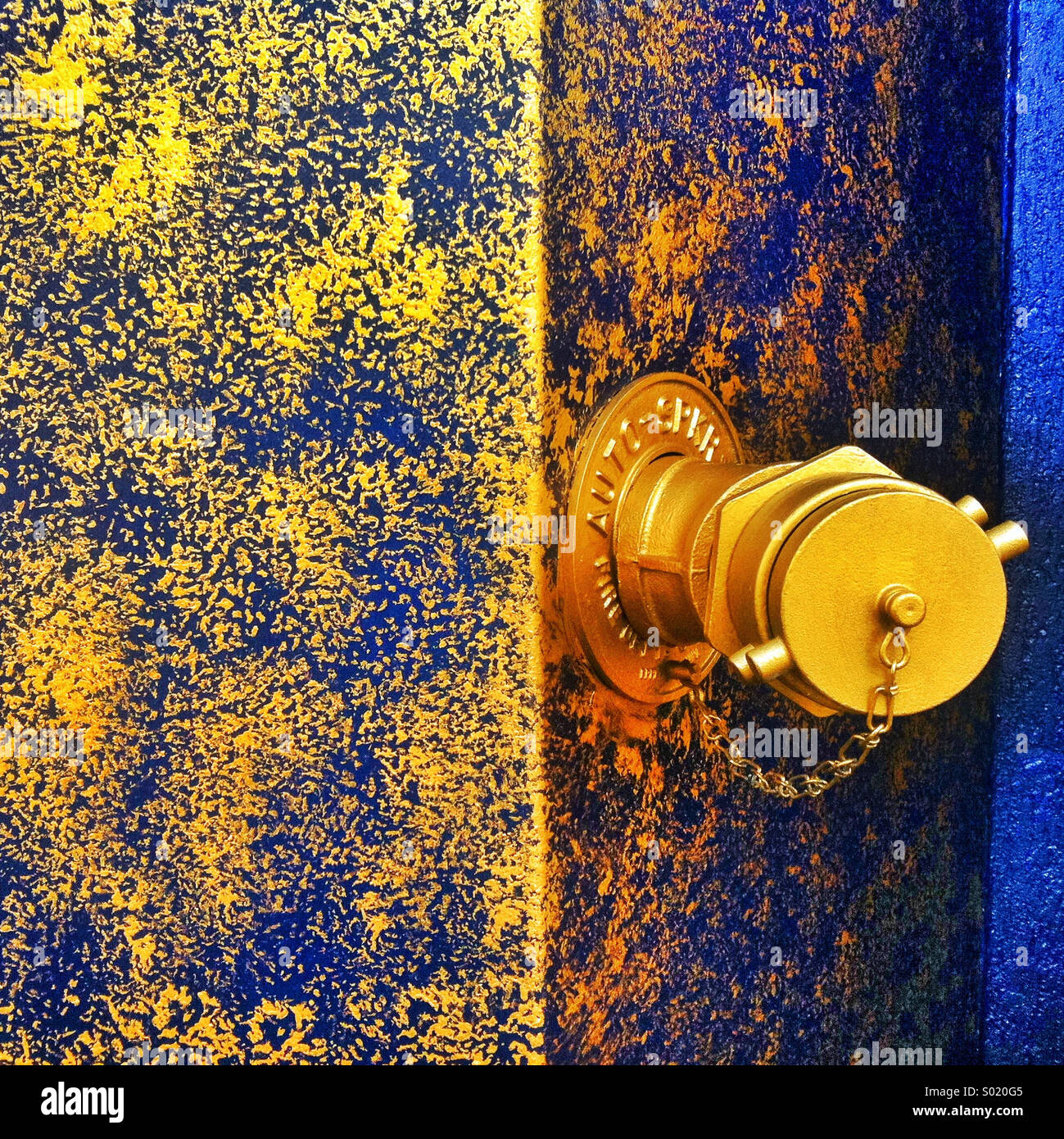A gold water spigot protrudes from a blue  building painted with gold paint - Stock Image