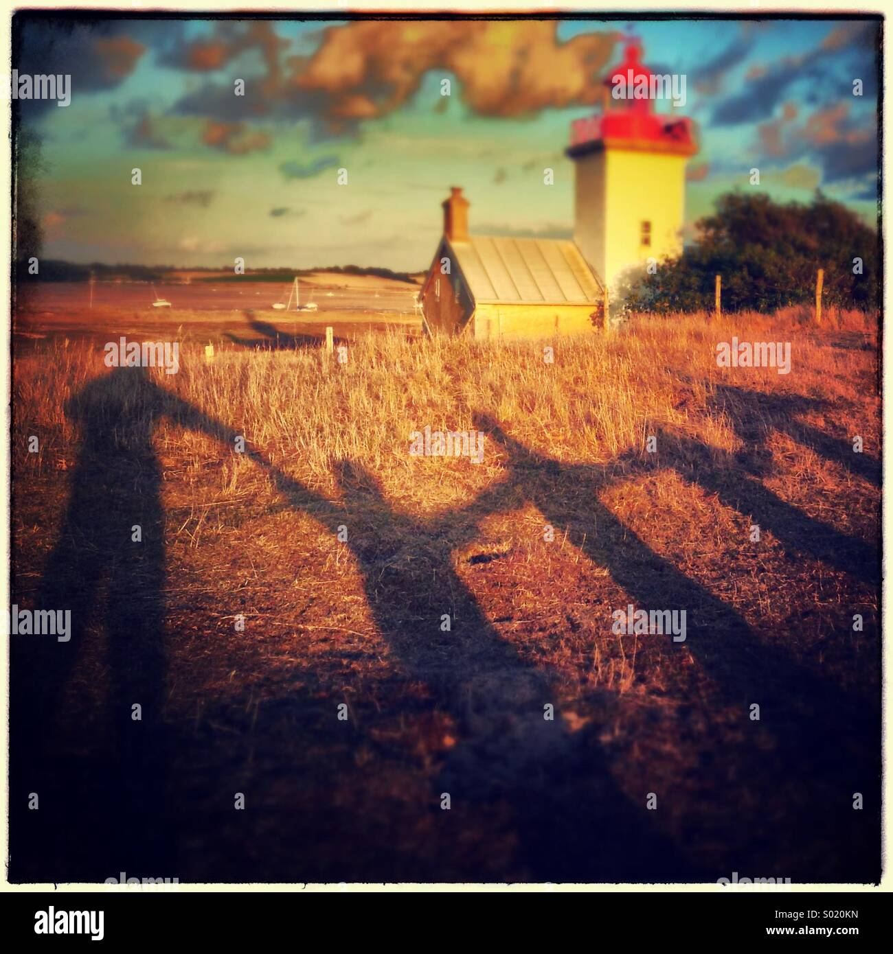 Family shadows in front of lighthouse in Agon, France Stock Photo