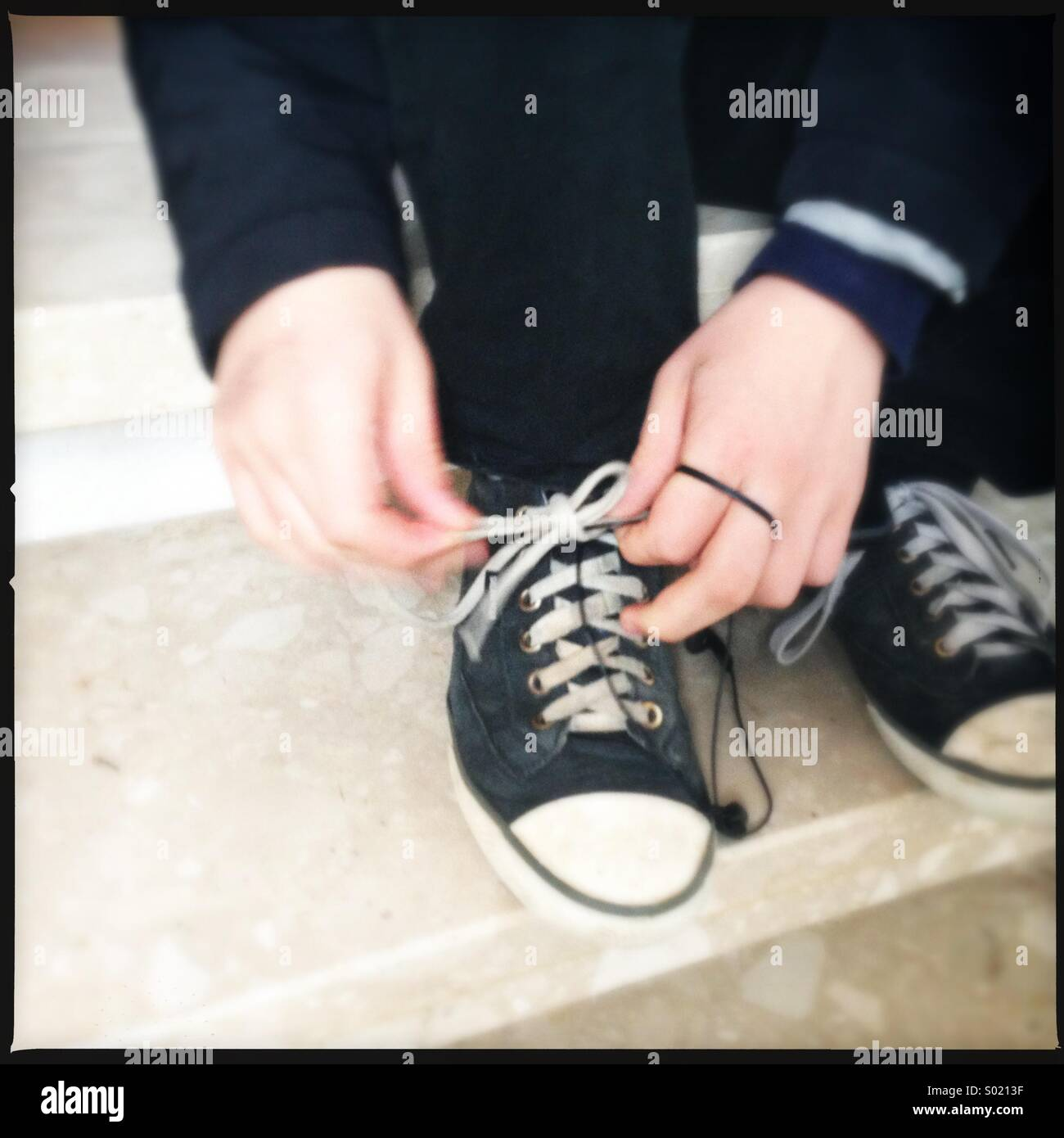 Boy fasten his shoes - Stock Image