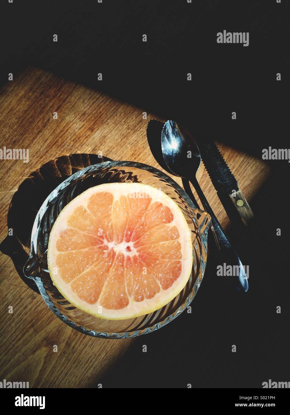 Pink grapefruit with grapefruit spoon and knife on a table. - Stock Image