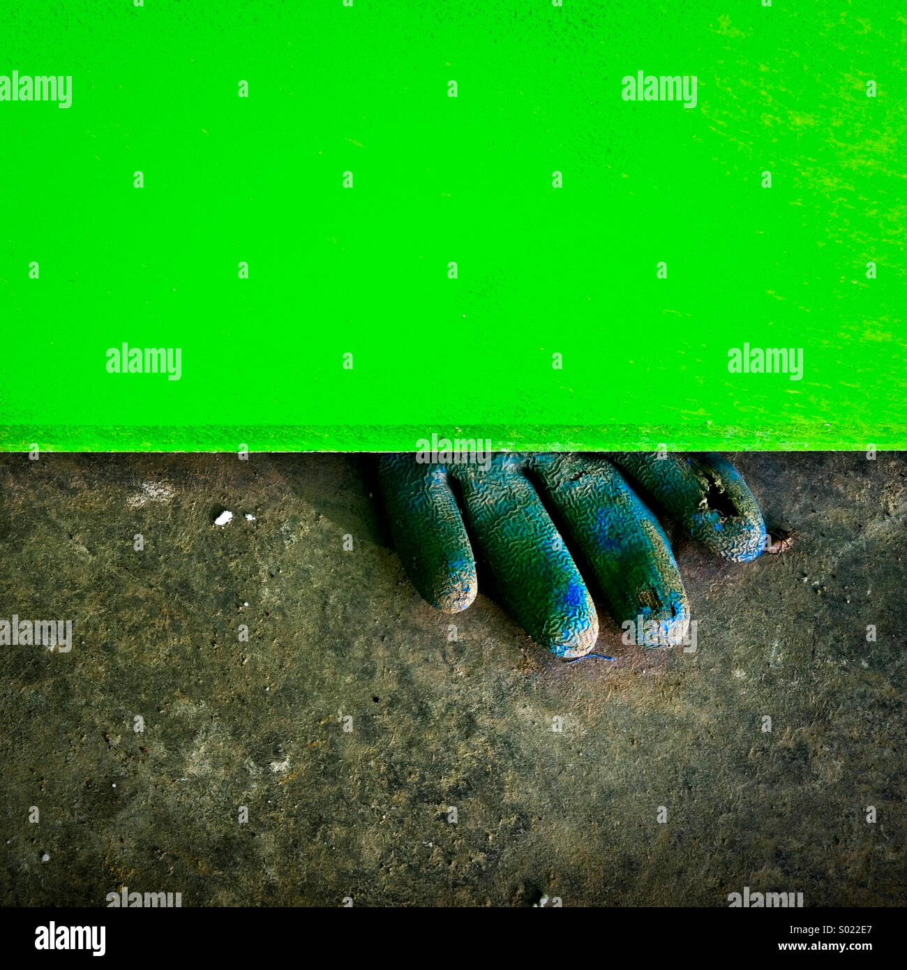 A dirty blue rubber glove peeks out from beneath a green board - Stock Image