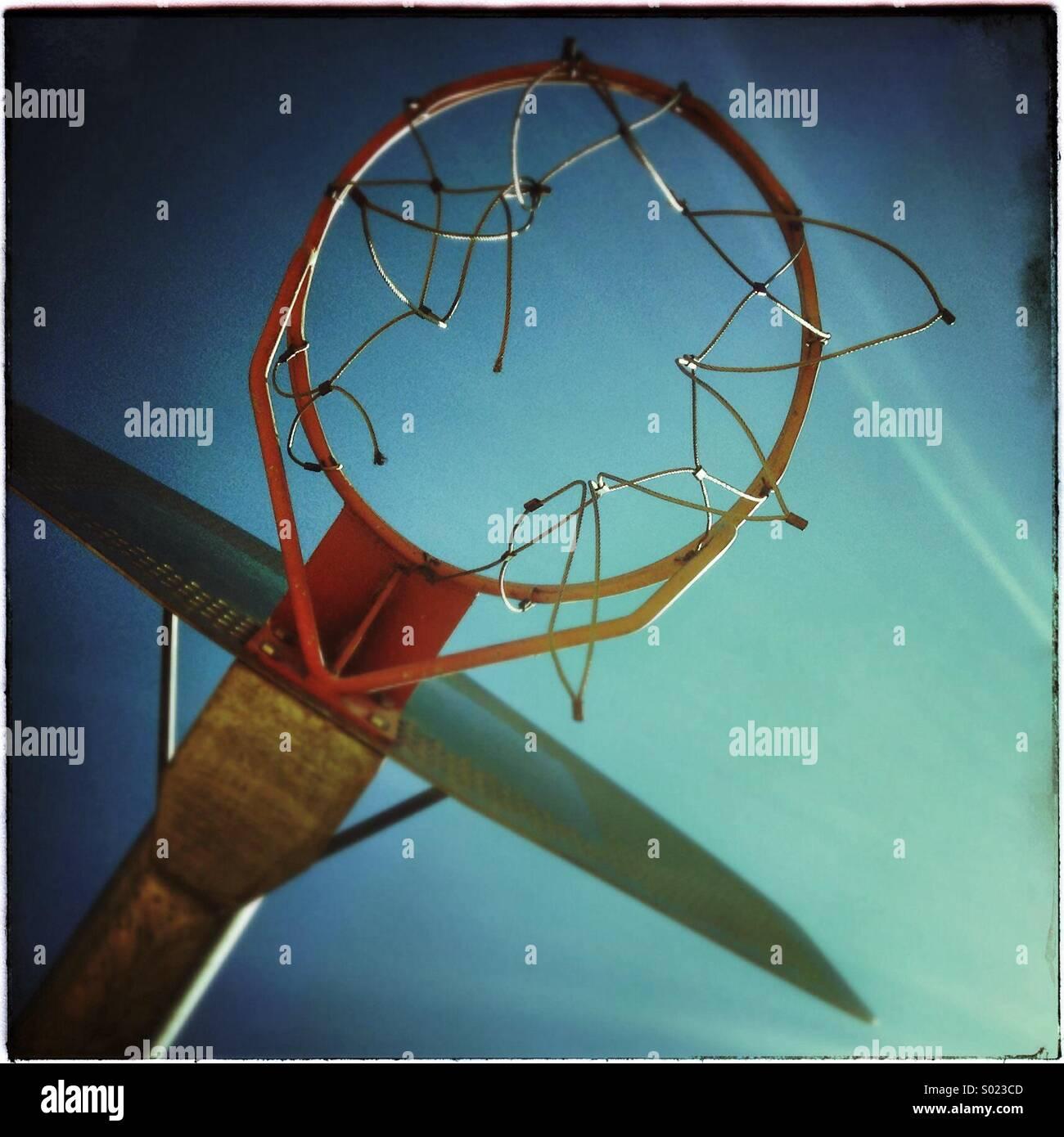 Basketball hoop on a clear blue sky - Stock Image