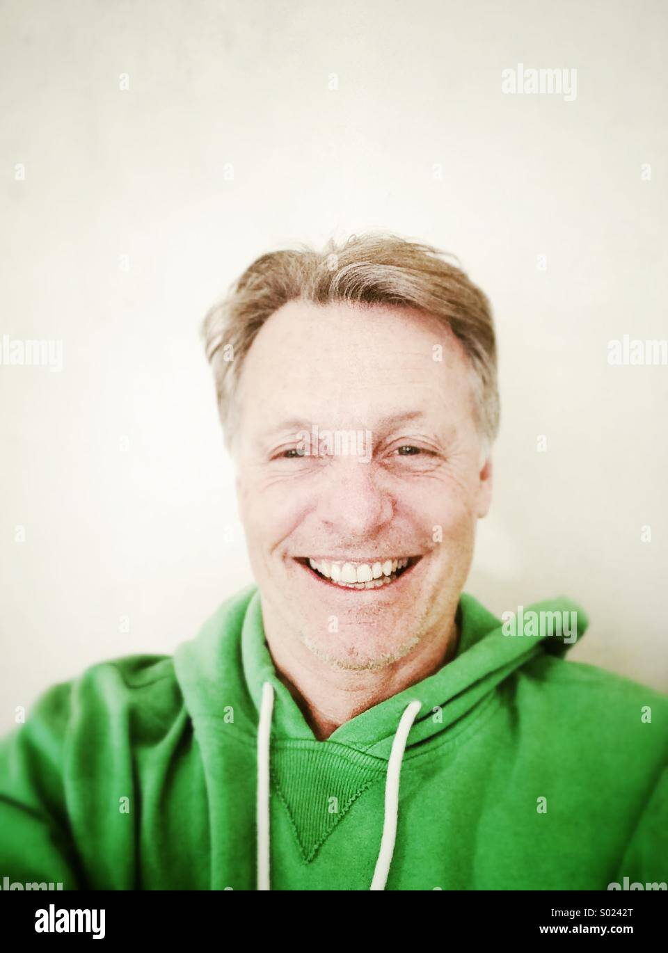Happy smiling mature man in his forties wearing a green hooded top. - Stock Image
