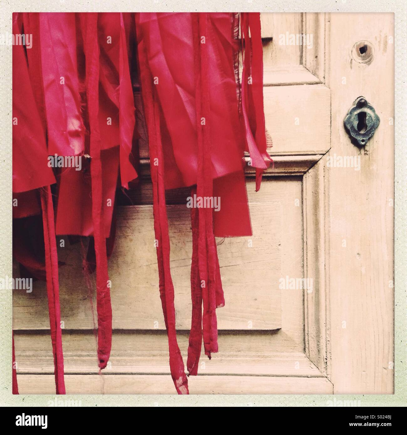 Red costume on old wooden door - Stock Image