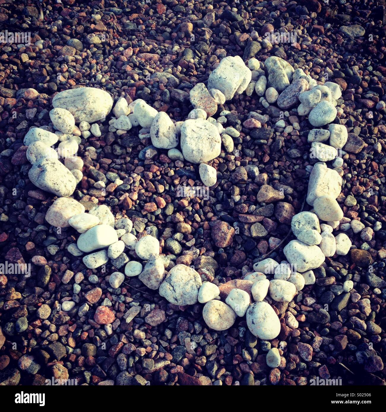 A heart made of white stones and pebbles on a colourful beach - Stock Image