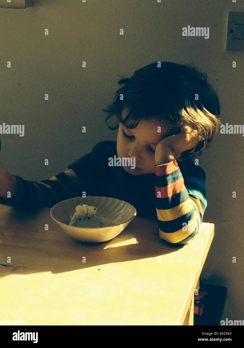 Boy eating ice cream in sunbeam with stripe top. - Stock Image
