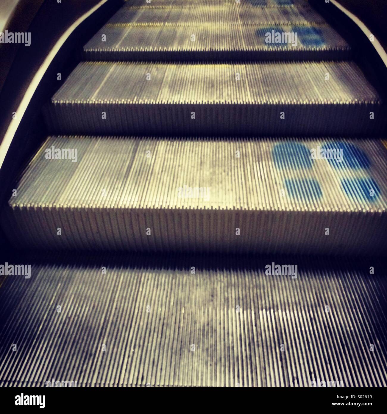 Close-up of escalator steps with footprints. - Stock Image