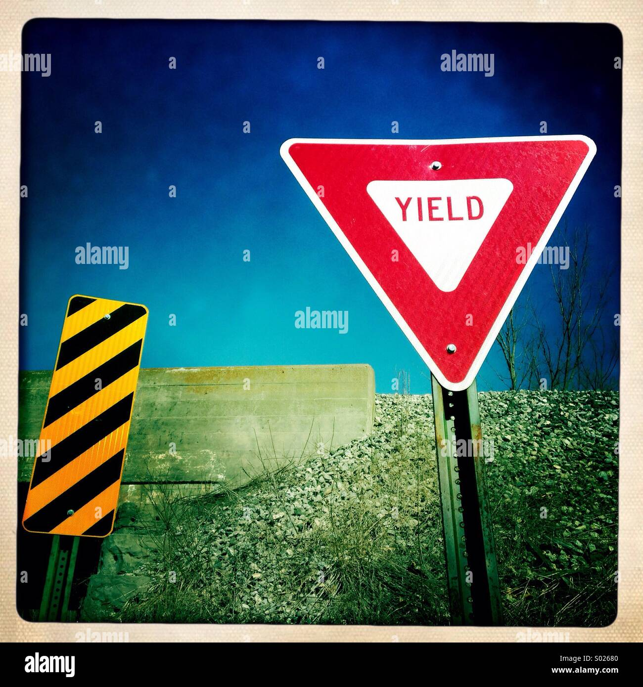 Yield sign against a blue sky. - Stock Image