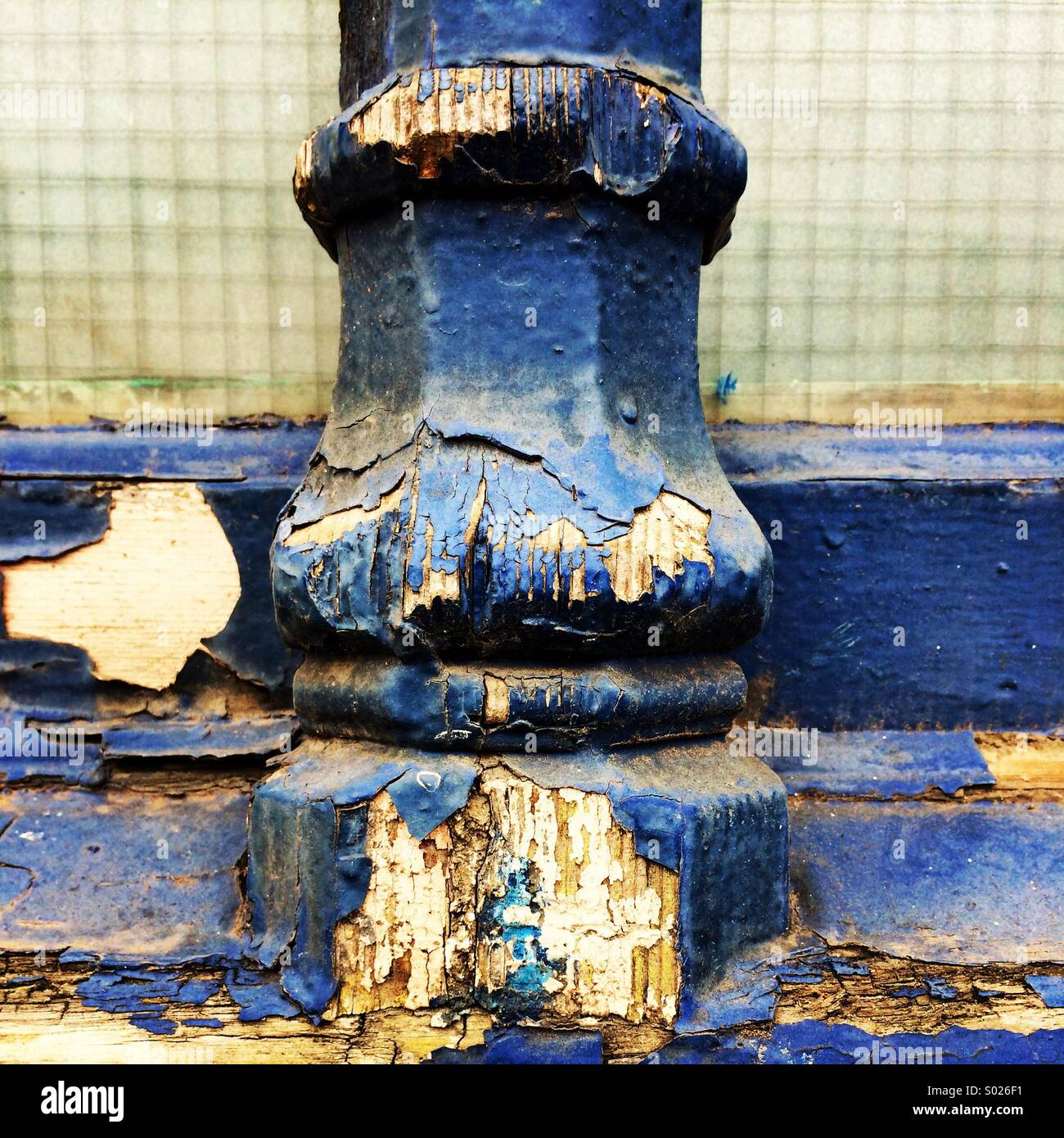 Peeling and flaking blue paint on an ornate window frame. - Stock Image