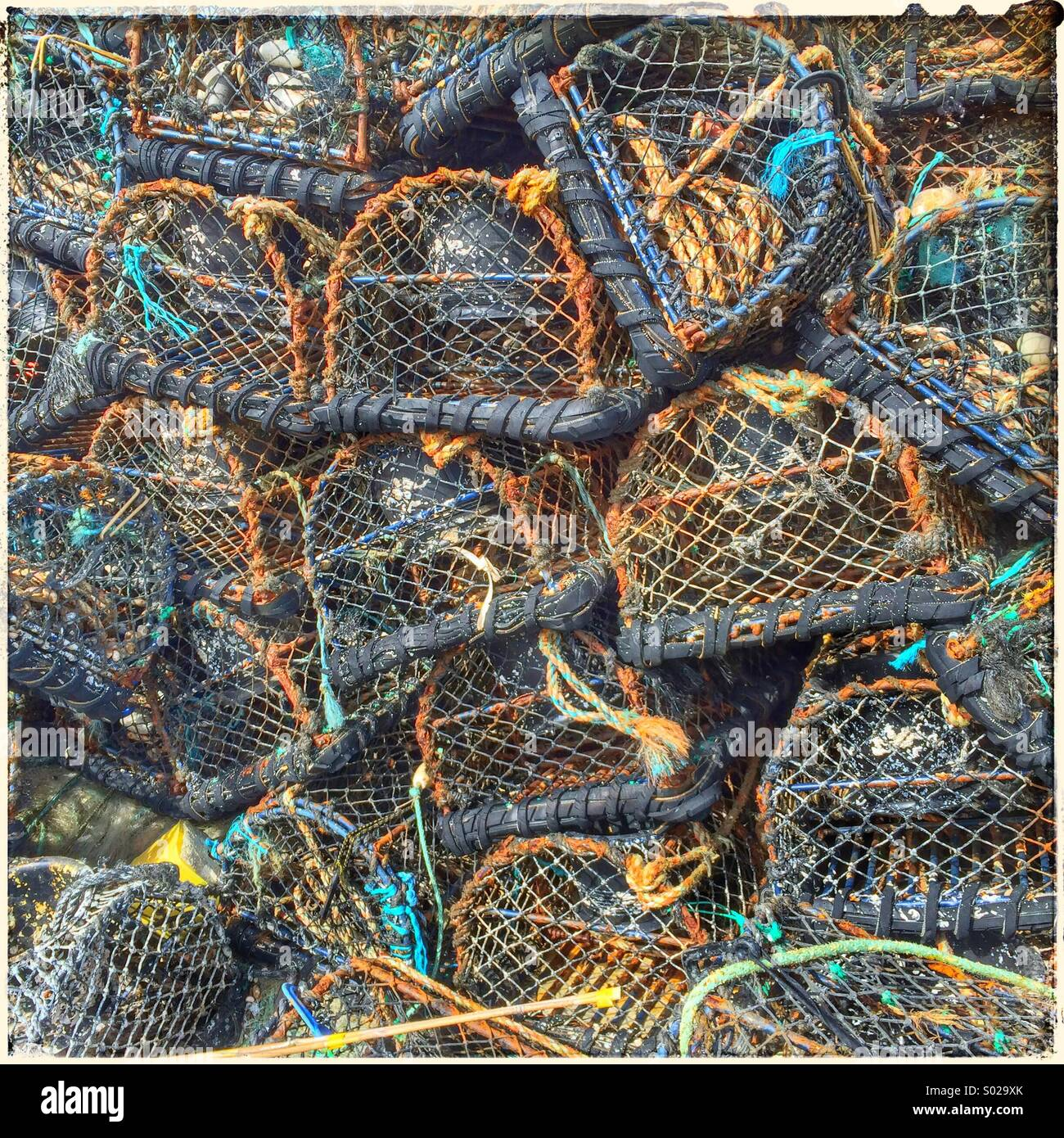 Lobster and crab fishing pots piled up on beach - Stock Image