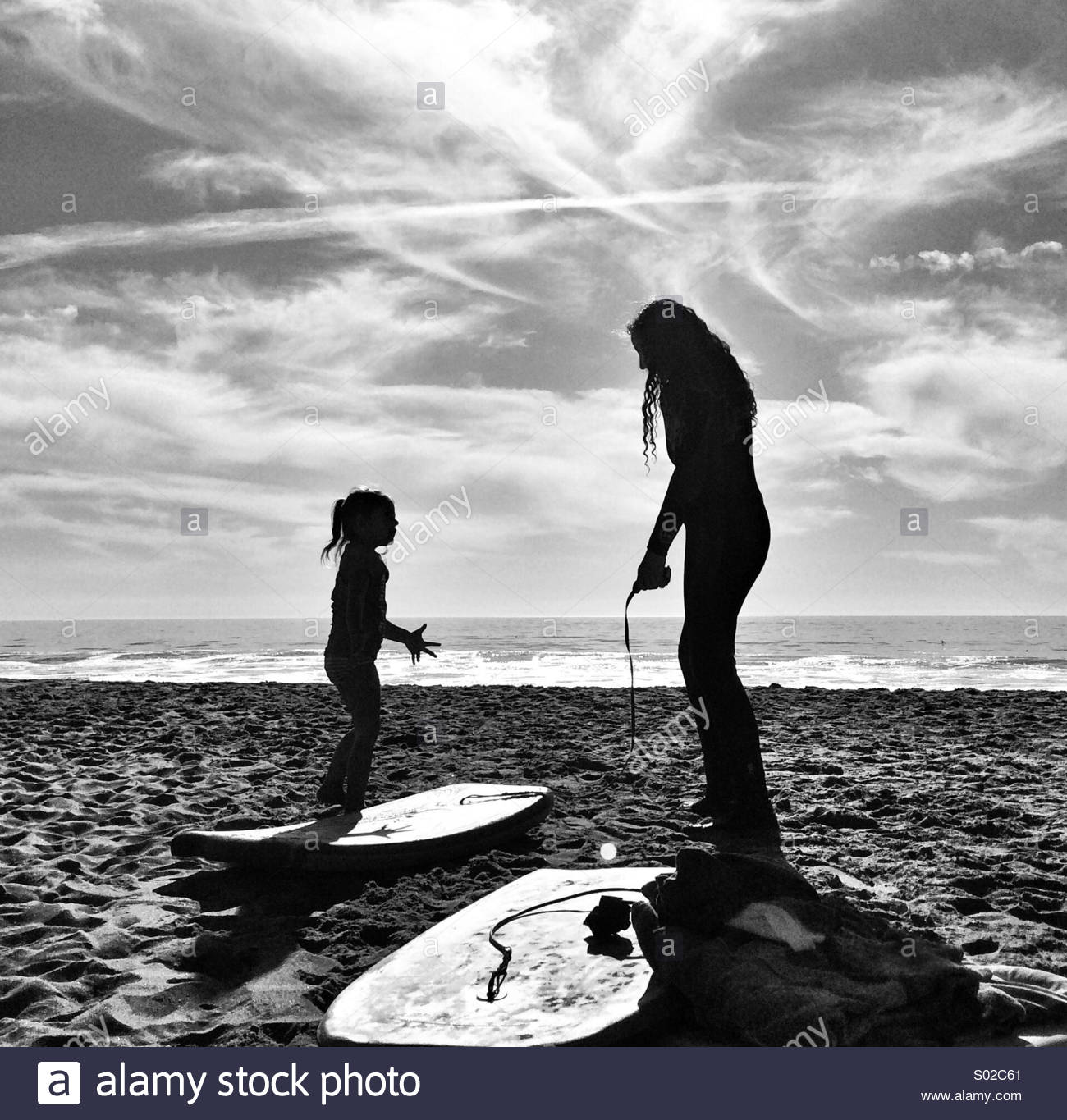 Two Girls On Beach Ready To Boogie Board - Stock Image